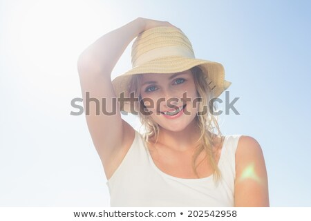 Portrait of gorgeous young Caucasian woman smiling and looking at camera on beach. It is sunny day Stock photo © wavebreak_media