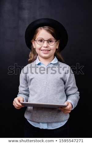 Pretty little girl looking at you with toothy smile while using digital tablet Stock photo © pressmaster