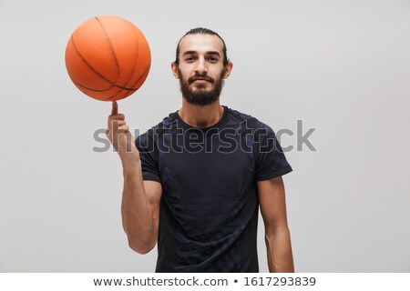 Image of young pleased man in sportswear doing exercise with basketball Stock photo © deandrobot
