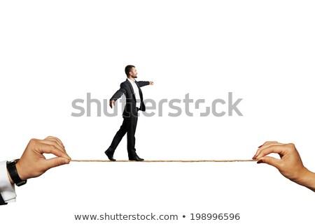 Man walk the walk the tightrope isolated on white background. Stock photo © Leonardi