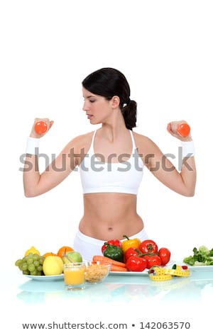 woman lifting weights surrounded by vegetables stock photo © photography33