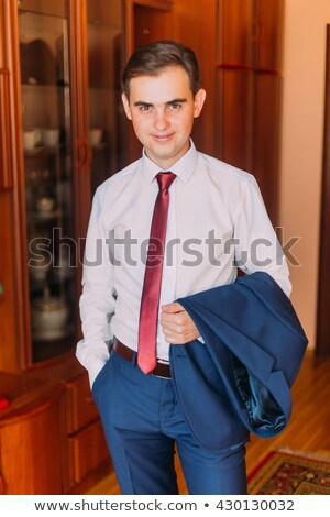 good looking man in a suit holding his jacket over his shoulder stock photo © photography33