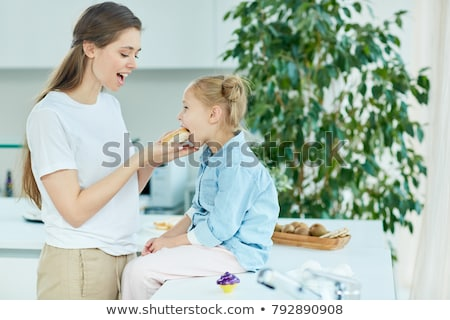 Mother giving her daughter a snack Stock photo © photography33