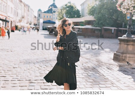 beautiful attractive woman in black dress turning around stock photo © feelphotoart