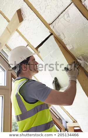 builder fitting insulation boards into roof of new house stock photo © highwaystarz