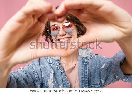 Attractive girl with pink heart in hands smiling stock photo © nyul
