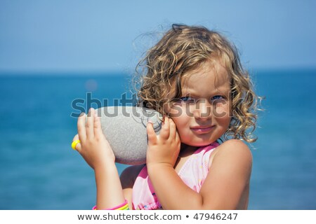 pretty little girl holds in hands pebble on seacoast in afternoo Stock photo © Paha_L
