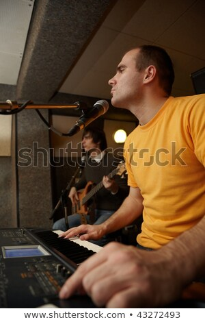 keyboarder is playing near microphone guitar player in out of focus stock photo © paha_l