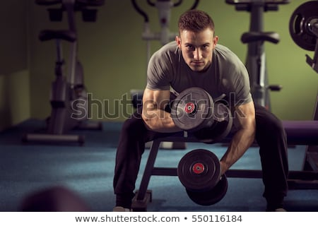 concentrated muscular man lifting dumbbells stock photo © wavebreak_media