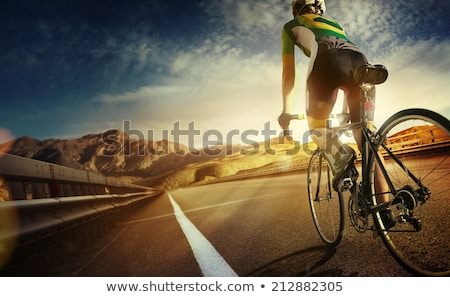 Stock photo: Woman cyclist riding a bike on a mountain road