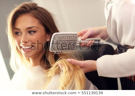 Female hairdresser brushing hair of smiling woman  Stock photo © deandrobot