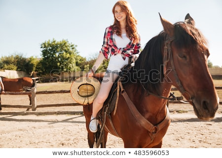 Smiling attrative young woman cowgirl riding horse Stock photo © deandrobot
