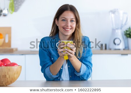 Happy girl holding tea cup and looking at camera indoors Stock photo © deandrobot