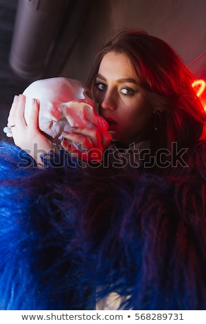 Woman outdoors at night. Holding artificial skull Stock photo © deandrobot