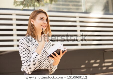 thoughtful business woman looks in her notebook reminder stock photo © nobilior