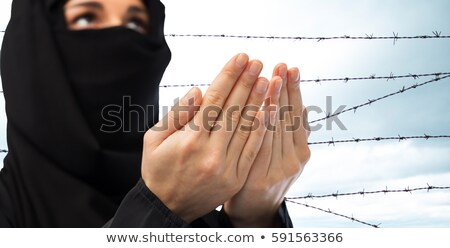 Stock photo: close up of praying muslim woman over barb wire