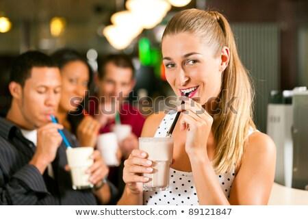 Ein junges Paar, das Milchshakes in einem Cafe trinkt Stock foto © Kzenon