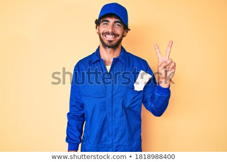 portrait of a joyful male builder pointing two fingers up stock photo © deandrobot