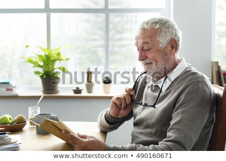 man reading book to senior woman stock photo © is2