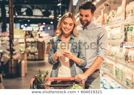 Couple in supermarket reading shopping list stock photo © deandrobot