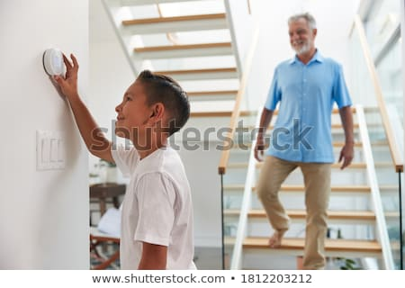 child Adjusting Thermostat On Central Heating Control stock photo © Lopolo