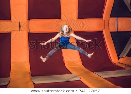 Young woman sportsman jumping on a trampoline in fitness park and doing exersice indoors Stock photo © galitskaya