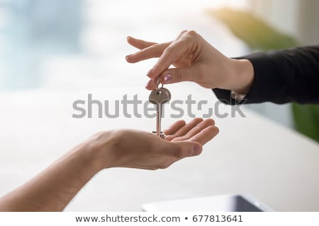 Real estate agent giving keys to apartment owner, buying selling property business. Close up of male Stock photo © galitskaya