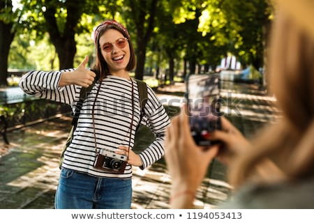Stockfoto: Pretty Ladies Friends Walking Outdoors With Backpacks Take A Photo By Mobile Phone