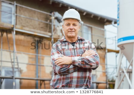 Proud plasterer standing in front of scaffold on construction site Stock photo © Kzenon