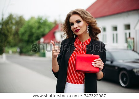 Fashionable woman holding red clatch and showing super by finger. Stock photo © studiolucky