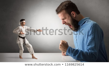 Stock photo: Giant man yelling at a small karate man