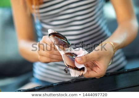 Women hands cleaning protective sunglasses with micro fiber wipe Stock photo © adamr