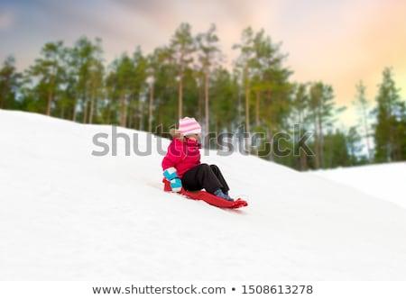 happy little girl sliding down on sled in winter Stock photo © dolgachov