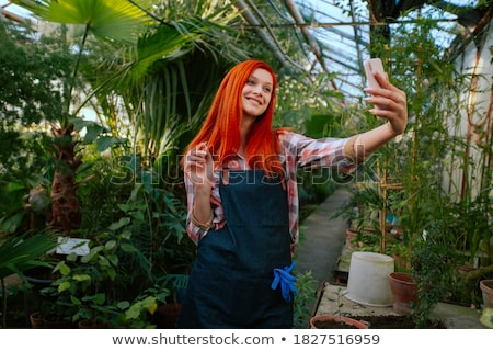 gardener woman in her shop taking care of some flowers stock photo © kzenon