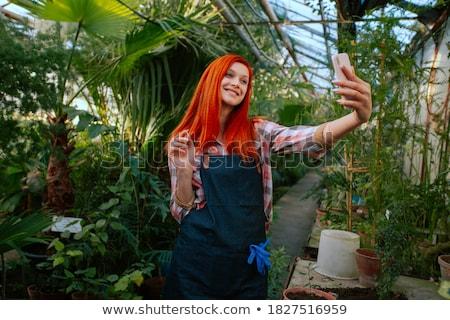 Gardener woman in her shop taking care of some flowers Stock photo © Kzenon