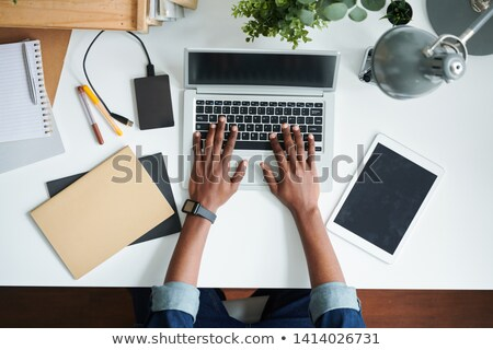 Overview of human hands on laptop keypad during network by desk Stock photo © pressmaster