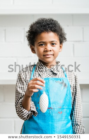 African youngster in blue apron holding white painted handmade xmas decoration Stock photo © pressmaster