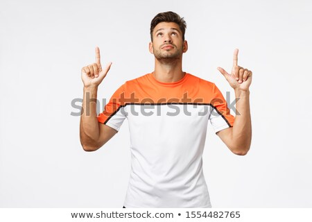 Handsome caucasian bearded sportsman, masculine guy in activewear looking up, pointing top advertise Stock photo © benzoix