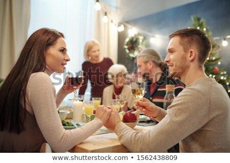 Young affectionate couple with glasses of wine making toast by served table Stock photo © pressmaster