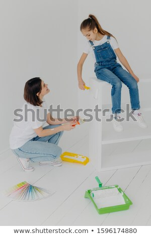 Shot of little girl sits on white furniture, refurbish drawer together with mother, use paint roller Stock photo © vkstudio