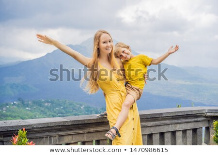 Mom and son tourists on background looking at Batur volcano. Indonesia. Traveling with kids concept  Stock photo © galitskaya