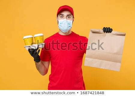 Delivery man in protective mask and gloves, employee hold takeaway cup of coffee, coronavirus Stock photo © Illia