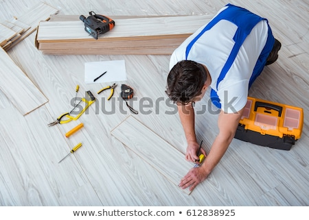 Stock photo: man sawing parquet plank