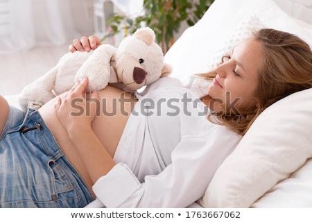 hamile · kadın · bakıyor · göbek · stüdyo · fotoğraf · yalıtılmış - stok fotoğraf © filipw