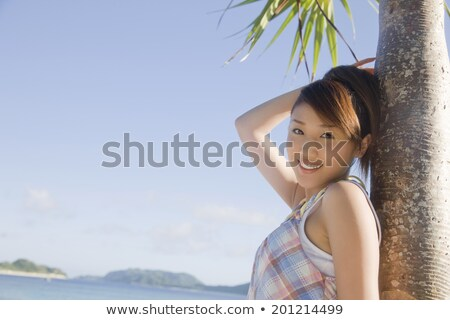 Woman leaning against palm tree Stock photo © photography33