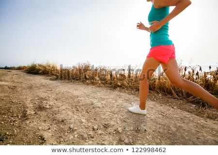 Young woman on her evening jog along the seacoast ( Stock photo © lightpoet