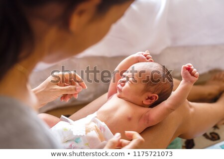 newborn infant baby girl in mothers caring arms wearing diaper stock photo © cboswell