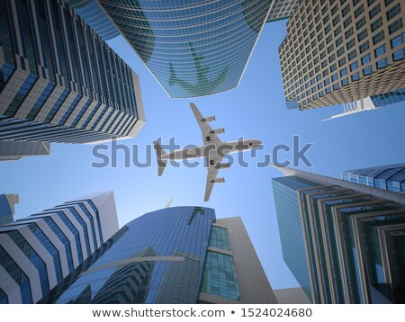 Airliner flying over high office buildings Stock photo © mikdam