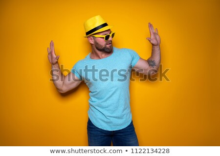 muscular man posing in blue jeans hat and sunglasses stock photo © wavebreak_media