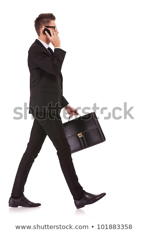 full length portrait of a man walking on talking on the phone stock photo © deandrobot